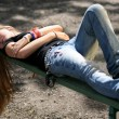 teen beauty lying on park bench